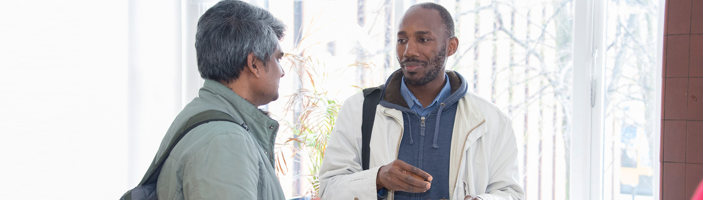 Two men chatting at a CRESC event