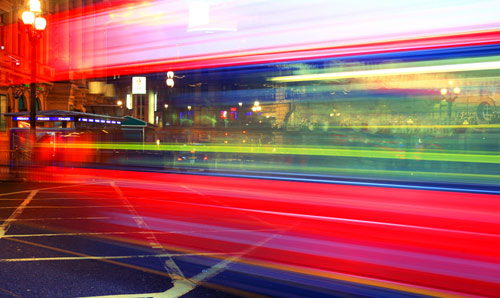 A blurred time-lapsed photograph of a London bus and cityscape