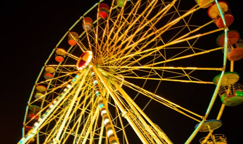 A photograph of a ferris wheel at night
