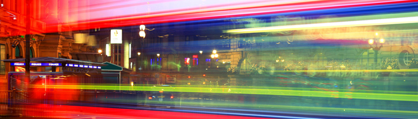 A blurred time-lapse view of a London bus and cityscape
