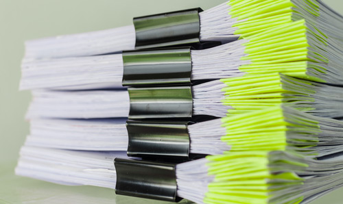 Photograph of a large pile of files or reports